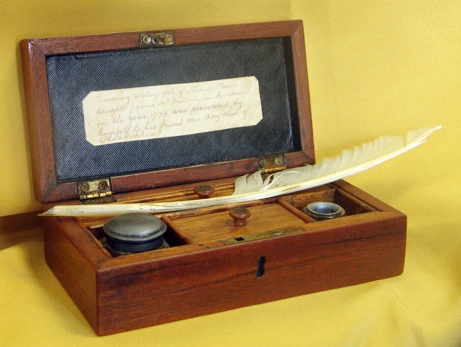 Image of Thomas Paine's writing desk, open with feather quill and ink pot visible